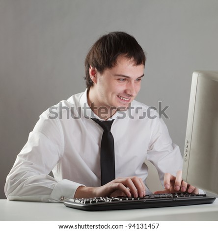 young man at the computer happy, looking at the monitor - stock photo