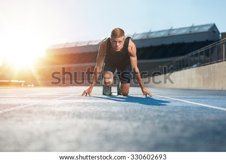 Young man athlete in starting position ready to start a race. Male sprinter ready for a run on racetrack looking at camera with sun flare. - stock photo