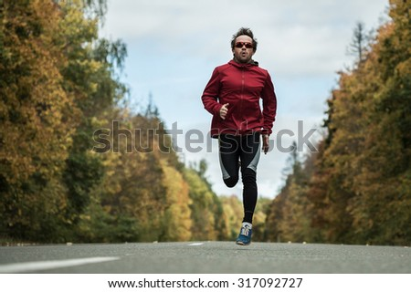 Young man athlete running hard on the asphalt road in the autumn forest - stock photo