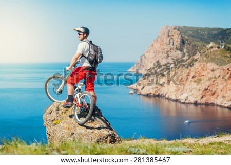 Young man athlete standing on top of a mountain with bicycle and enjoying view. - stock photo