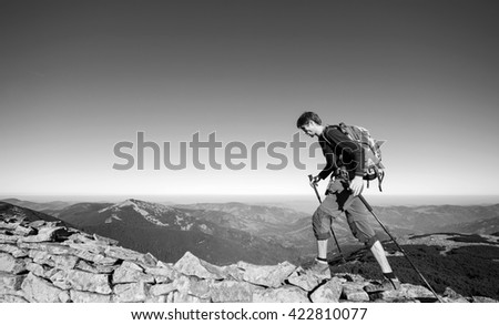Young man backpacker walking on the rocky ridge of the mountain with beautiful high altitude landscape view on the background. Hiker using trekking sticks. black and white - stock photo