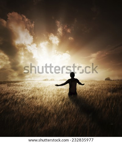 Young man basking the the glory of a beautiful sunset. - stock photo