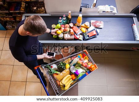 Young man before checkout in supermarket - stock photo