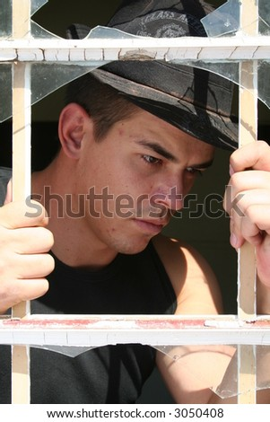 Young man behind bars en broken window - stock photo