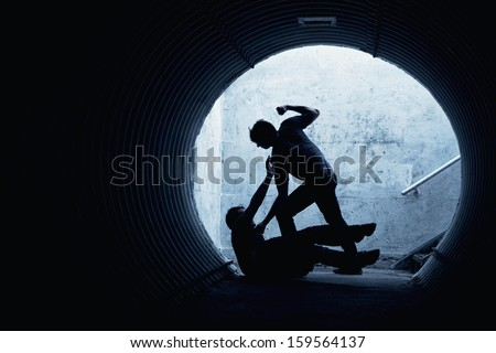 Young man being mugged in a dark tunnel by a violent man - stock photo