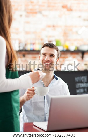 Young man being served at cafe - stock photo