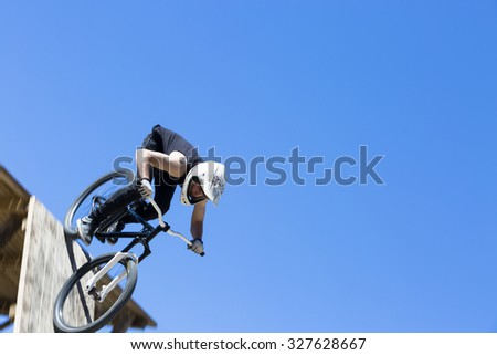 young man BMX rider is going down a wooden ramp on a BMX session in the mountain - focus on the helmet - stock photo