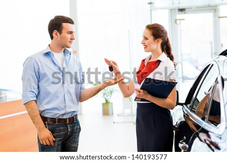 young man bought the car and takes the consultant keys from the new car - stock photo