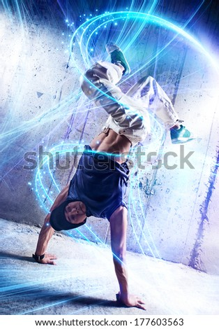 Young man break danceing on wall background. - stock photo