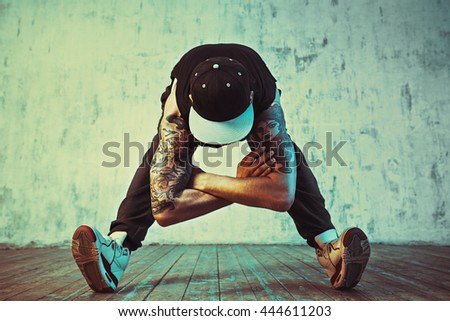 Young man break dancing on wall background. Blue and yellow colors tint. Tattoo on body. - stock photo