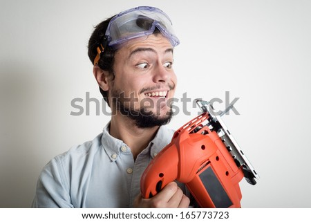 young man bricolage working with electric saw at home - stock photo