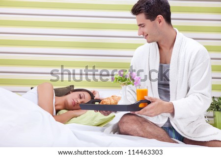 Young man bringing breakfast in bed his sleeping wife - stock photo