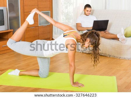 Young man browsing internet while girl doing yoga at home. Focus on girl