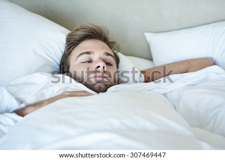 Young man busy looking out his apartment window while lying in his white bedding alone in the morning before work - stock photo