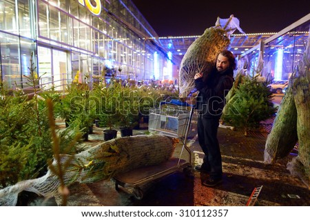Young man buying a Christmas tree in the store - stock photo