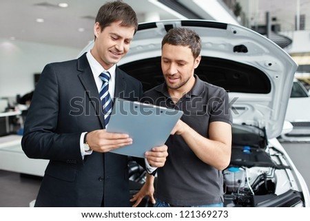 Young man buys a car - stock photo