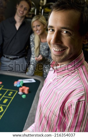 Young man by friends gambling at roulette table, smiling, portrait, close-up - stock photo