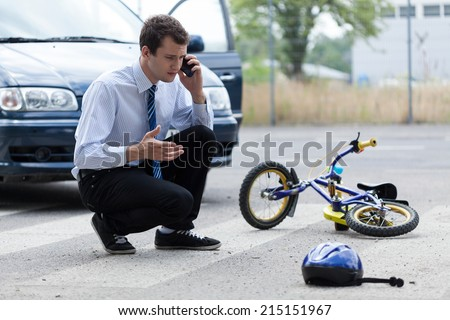 Young man calling for help after road accident - stock photo
