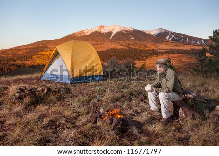 Young Man Camping and Sitting Next to Fire - stock photo