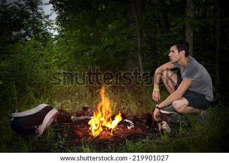 Young man camping in the mountains crouching alongside a burning campfire with his rucksack staring thoughtfully into the distance, profile view - stock photo