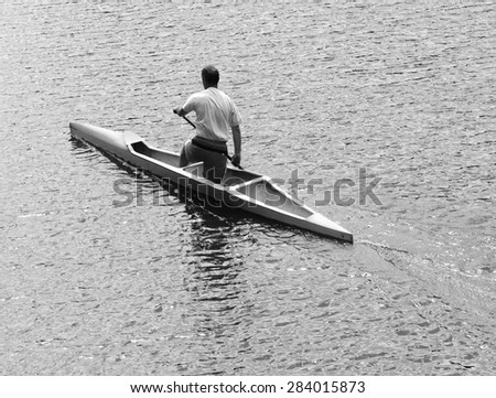 Young man canoeing in the lake at sunset. Classical black and white photography of high contrast scene. - stock photo