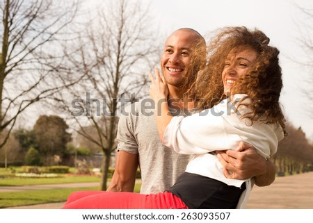 young man carrying his girlfriend in the park - stock photo