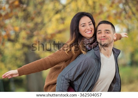 Young man carrying his girlfriend on back - stock photo