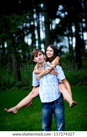 young man carrying his girlfriend on his back in park - stock photo