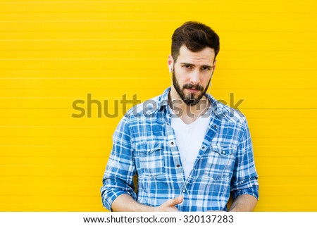 young man casual dressed with headphones and smart phone on yellow background - stock photo