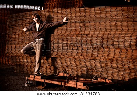 young man casual in shirt and pants, lean on rusty wire armature - stock photo
