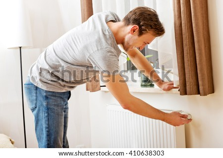 Young man changing temperature of radiator - stock photo