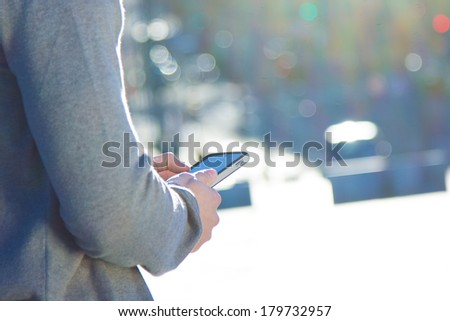 Young man chatting with their smartphone in the street - stock photo