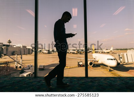 Young man checking his phone while waiting his flight in the airport - Business man at airport and airplane and airport in the background - stock photo