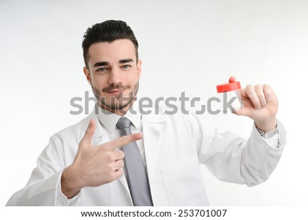 young man chemist on white coat showing bottle of pills - stock photo