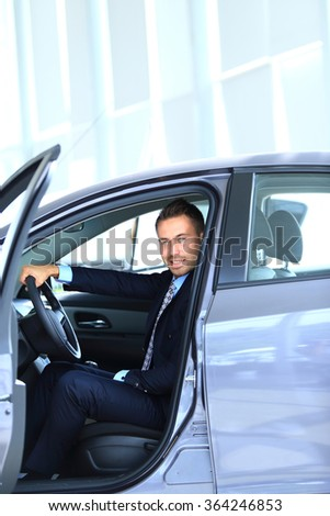 Young man choosing car at salon with help of consultant - stock photo