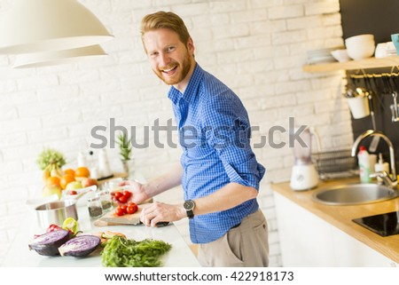 Young man chopping vegetables in the kitchen - stock photo