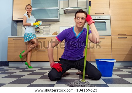 Young man cleaning floor with his girlfriend at kitchen - stock photo
