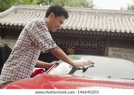 Young Man Cleaning His Car - stock photo