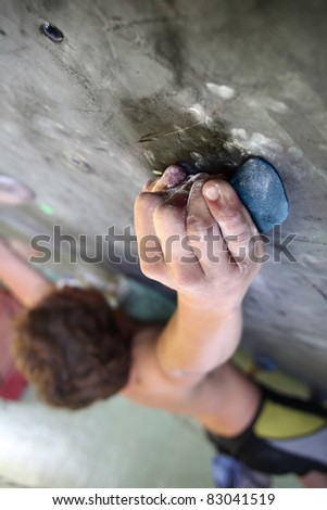 Young man climbing indoor wall - stock photo