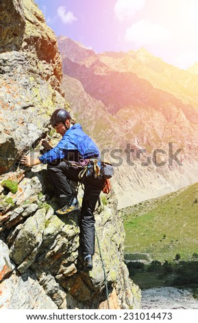 Young man climbing natural rocky - stock photo