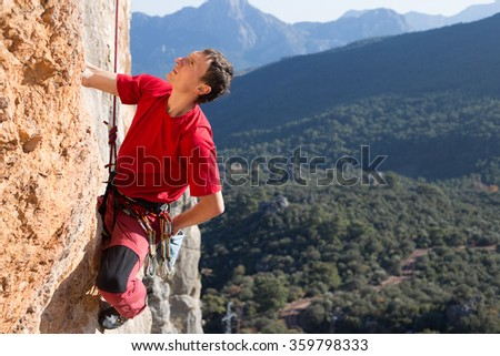 Young man climbing on a limestone wall with wide valley on the background. - stock photo