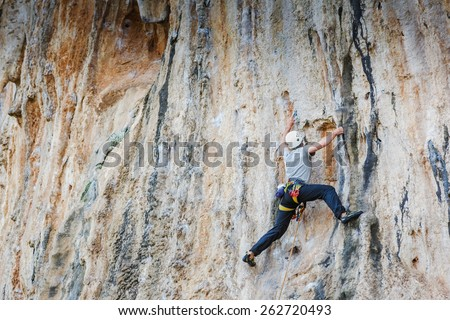 Young man climbing on a wall and quick-draws - stock photo
