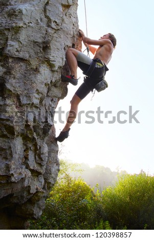Young man climbing vertical natural rocky wall with clear sky on the background - stock photo