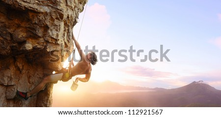 Young man climbing vertical wall with belay with sunrise valley on the background - stock photo