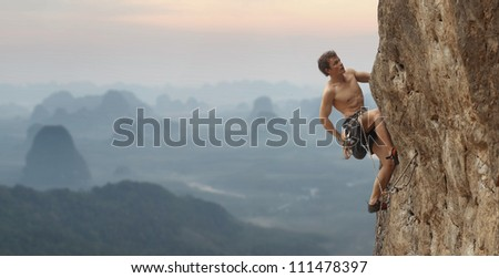 Young man climbing vertical wall with blurred valley view on the background - stock photo