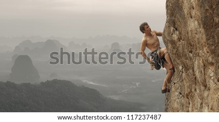 Young man climbing vertical wall with valley view on the background - stock photo