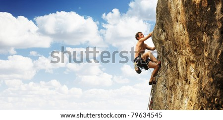 Young man climbs on a cliff over blue sky background - stock photo