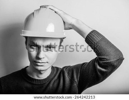Young man close-up in yellow construction helmet and  headache, holding his head by hand. Mimicry. Gesture. photo Shoott - stock photo