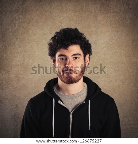 Young man close up portrait with perplexed expression against grunge background. - stock photo