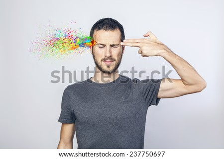 young man committing suicide with finger gun gesture, explosion of colors - stock photo